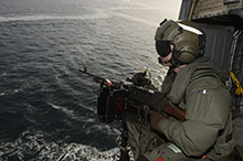 The coastal waters of Scotland. 7 October 2015 – Corporal Dustan Cooper, an Airborne Electronic Sensor Operator on board Her Majesty's Canadian Ship (HMCS) WINNIPEG's CH-124 Sea King helicopter, intercepts a simulated fast attack craft strike with a C6 machine gun during Exercise JOINT WARRIOR 152 over the course of Operation REASSURANCE. (Photo by: Cpl Stuart MacNeil, HMCS WINNIPEG)