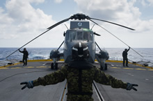 Europe. 7 July 2015 - Under the direction of the flight deck director, the flight deck hands unfold the rotor blades of Her Majesty's Canadian Ship WINNIPEG's CH-124 Sea King helicopter in preparation for take-off during Operation REASSURANCE. (Photo: Cpl Stuart MacNeil, HMCS WINNIPEG)