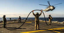 Members of Her Majesty's Canadian Ship (HMCS) FREDERICTON Air Detachment, perform a mid-air refueling with the CH-124 Sea King helicopter from the flight deck during Operation REASSURANCE on January 21, 2016. (Photo: Corporal Anthony Chand, Formation Imagery Services)