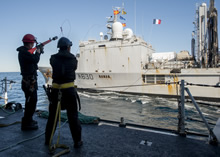 28 March 2015 – A Boatswain on board Her Majesty's Canadian Ship FREDERICTON fires a gun line to French supply ship FS MARNE during a liquid replenishment at sea during Operation REASSURANCE. (Photo: Maritime Task Force - OP REASSURANCE, DND)