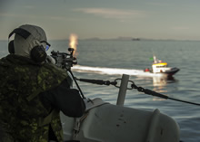 19 April 2015 - A crewmember from Her Majesty's Canadian Ship FREDERICTION engages a C9 machine gun during a simulated small boat attack during Exercise JOINT WARRIOR as part of their deployment on Operation REASSURANCE. (Photo: Maritime Task Force - OP Reassurance, DND)