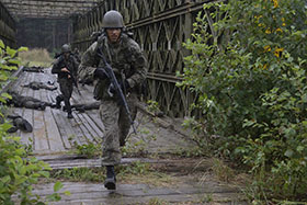 Eastern Europe. 30 June 2014 - Soldiers from the 16th Battalion of the Polish 6th Airborne Brigade cross a bridge as part of a joint Polish and Canadian exercise during Operation REASSURANCE. (Photo: Cpl Mark Schombs, 4 CDSG Garrison Petawawa Imaging)