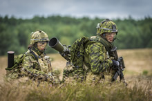 Glebokie, Poland. 31 July 2015 – Corporal Philippe Lyonnais carries a Carl Gustav recoilless rifle (M2CG) followed by Corporal Emilie Gauthier-Wong carrying the 84mm rounds for the M2CG during a live fire exercise at Mielno range in the Drawsko-Pomorski training area in Glebokie, Poland on July 31, 2015 during Operation REASSURANCE. Photo: Corporal Nathan Moulton, Land Task Force Imagery