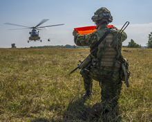 Hohenfels, Germany. 21 August 2015. Master Corporal Ian Chagnon identifies the landing area with an orange flag as a helicopter lands during Exercise ALLIED SPIRIT II at the Joint Multinational Readiness Center during Operation REASSURANCE (Photo: Corporal Nathan Moulton, Land Task Force Imagery).