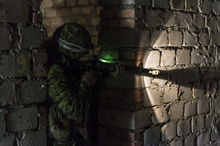 Ziemsko, Poland. 2 September 2015 – A soldier guards the door while his team conducts a room clearing scenario in a dark abandoned building during urban operations training at Mogadisz in Ziemsko, Poland during Operation REASSURANCE. (Photo: Corporal Nathan Moulton, Land Task Force Imagery, OP REASSURANCE)