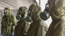 Kadaga, Latvia. 22 September 2015. Canadian Armed Forces members dress in full chemical, biological, radioactive and nuclear (CBRN) equipment during practice drills for Exercise SILVER ARROW at Adazi Military Training Area in Kadaga, Latvia during Operation REASSURANCE (Photo: Corporal Nathan Moulton, Land Task Force Imagery, OP REASSURANCE).