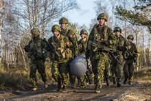 Canadian and Polish Armed Forces members compete as a team to carry a weighted load, 1.5 km during an exercise at Nowa Dęba Training Center in Nowa Dęba, Poland on December 2, 2015 during Operation REASSURANCE. (Photo: Corporal Nathan Moulton, Land Task Force Imagery, OP REASSURANCE)