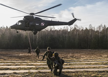 Canadian and Polish Armed Forces members decend from a helicopter on a rope during a fast rope exercise at Nowa Dęba Training Center in Nowa Dęba, Poland on December 4, 2015 during Operation REASSURANCE. (Photo: Corporal Nathan Moulton, Land Task Force Imagery, OP REASSURANCE)
