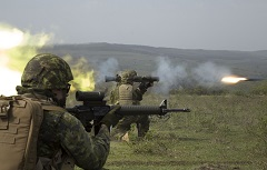 April 9 2016. Cincu, Romania. Corporal Michaël Lafrenais-Dietrich of the Voltigeurs de Québec and Private Simon Tremblay of the 1st Battalion, Royal 22e Régiment (in background) fire the Carl Gustav short-range anti-armoured weapon, as Corporal Sonny Gauthier of 5e Ambulance de campagne (in foreground) supports their efforts, during a live-fire frontal assault exercise on a firing range in Cincu, Romania on April 9, 2016 during Operation REASSURANCE. (Photo: Corporal Guillaume Gagnon, Liaison Officer Driver, Operation REASSURANCE Land Task Force)