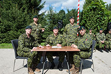 August 24 2016. From left to right, Major (Maj) Lonnie Campbell, Master Warrant Officer (MWO) Chris Thorne, Colonel (Col) Pascal Demers, MWO Martin Higgins and Maj Felix St-Jean sign the Transfer of Command Authority (TOCA) certificates in Drawsko Pomorskie Training Area, Poland on August 24, 2016 during Operation REASSURANCE. (Photo: Cpl Jay Ekin, Operation REASSURANCE Land Task Force Imagery Technician)