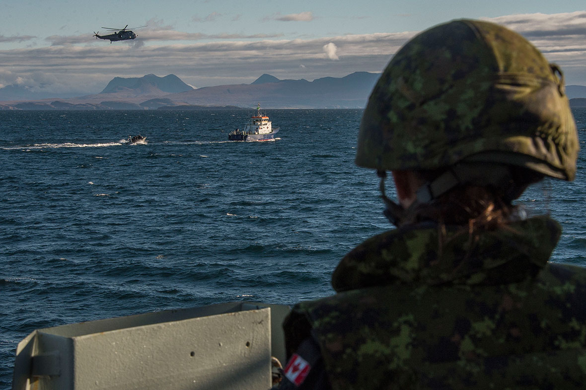 A sailor watches as a helicopter and a speed boat approach a medium sized boat