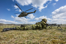 Poland. 28 April 2015 - A member of 3rd Battalion, The Royal Canadian Regiment (3 RCR) covers the arrival of a Polish helicopter at the Drawsko Pomorski training area during Operation REASSURANCE. (Photo: Land Task Force - OP Reassurance, DND)