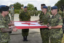 Campia Turzii, Romania. 22 August 2014 - Members of the Canadian Air Task Force (CATF) Romania fold the Canadian Flag at the closeout ceremony for the CATF's mission in Romania during Operation REASSURANCE. (Photo: Cpl Jean Archambault, ATF 1401 Imagery Technician)