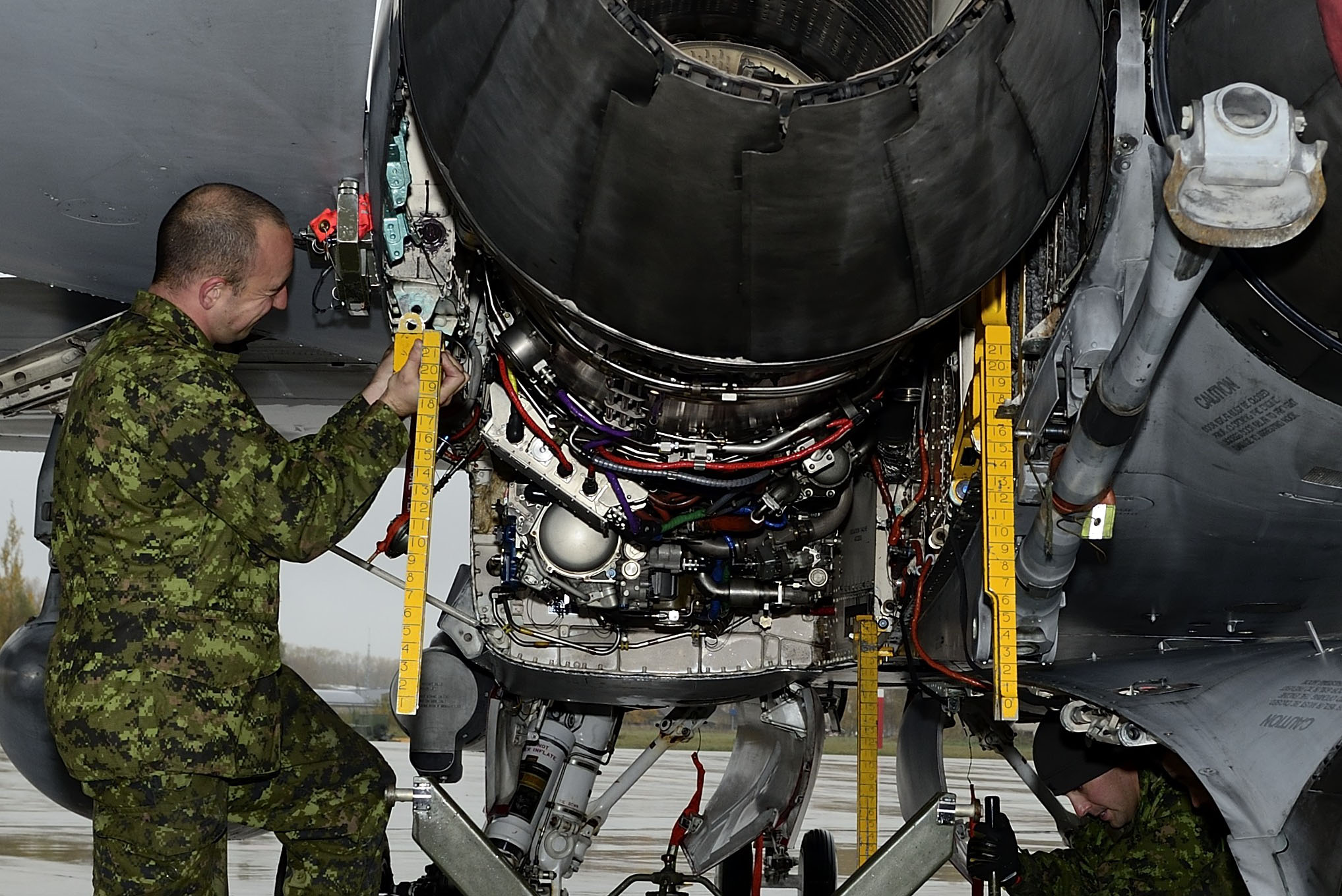 Šiauliai Air Base, Lithuania. 15 October 2014 – A member of the Canadian Air Task Force installs the engine guide rails in preparation to remove a CF-188 Hornet engine at Šiauliai Air Base, Lithuania during Operation REASSURANCE, in support of NATO Baltic Air Policing Block 36. (Photo: Cpl Gabrielle DesRochers)