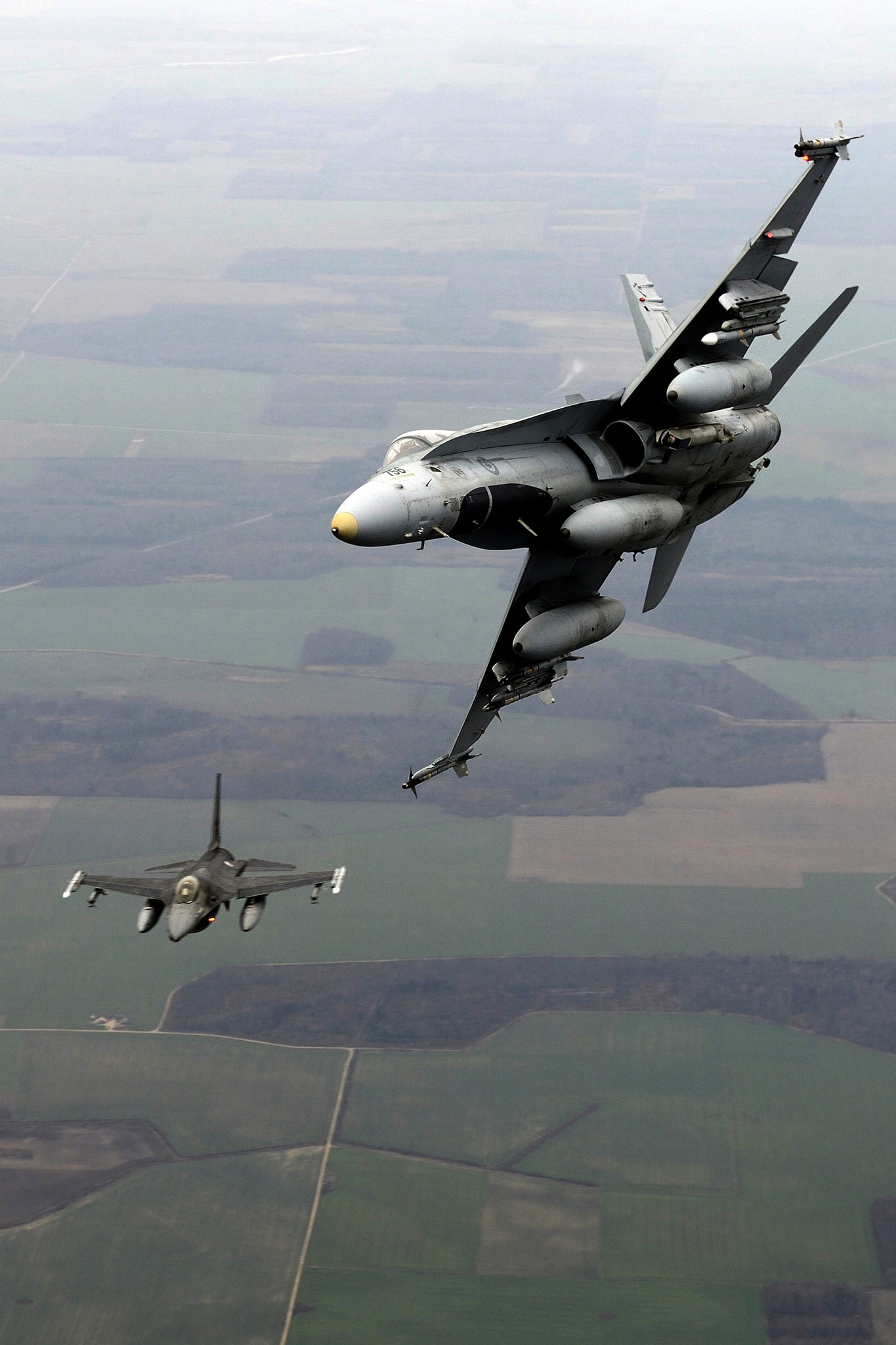 Lithuania. 20 November 2014 – A CF-188 Hornet from the Canadian Air Task Force Lithuania flies side by side with a Portuguese F16 Fighting Falcon over Lithuania on November 20, 2014 for the NATO Baltic Air Policing Block 36 during Operation REASSURANCE. (Photo: Air Task Force — OP Reassurance, DND)