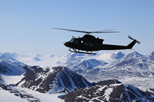 "Ellesmere Island. 18 June 2015 – A ""FREEDOM 53"" CH-146 Griffon helicopter from 408 Tactical Helicopter Squadron is shown flying above the United States Mountain Range on the northern portion of Ellesmere Island during Operation NEVUS 2015. The United States and British Empire mountain ranges are found on the northwest area of Ellesmere Island. (Photo:  Lieutenant-Navy Clayton Erickson, Joint Task Force (North))"