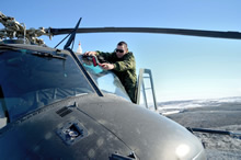 Corporal Fred Racine, an Aviation Technician from 438 Squadron based out of St Hubert Quebec cleans the windows of a CH-146 Griffon helicopter prior to taking off towards the Grant High Arctic Data Communications System (HADCS) on June 11, 2016 during Operation NEVUS. (Photo: PO2 Belinda Groves, Task Force Imagery Technician)