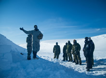 Resolute Bay, Nunavut. 4 April 2016. American Staff Sergeant Matt Hinds of the Northern Warfare Training Center instructs members of the 2nd Battalion, The Royal Canadian Regiment on the construction of a snow cave near Resolute Bay, NU, in preparation for Operation NUNALIVUT April 4, 2016. (Photo: Cpl Parks, Task Force Image Technician)
