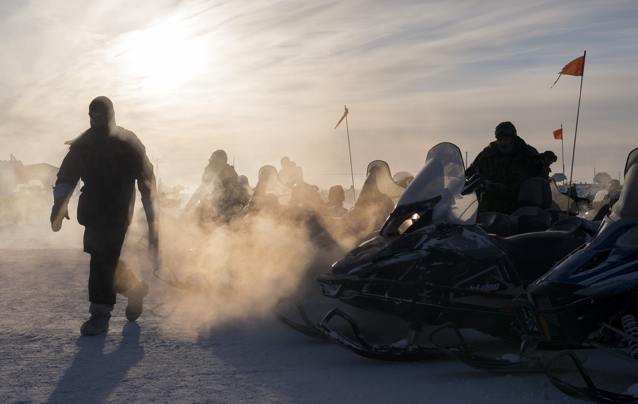 Deployed members from 12e Régiment blindé du Canada warm up the engines of Light Over Snow Vehicles in preparation for a patrol during Operation NUNALIVUT 2017 in Hall Beach, Nunavut February 24, 2017. Photo: Sgt Jean-François Lauzé, Task Force Imagery Technician