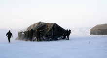 Deployed members from 12e Régiment blindé du Canada secure a modular tent in high winds during Operation NUNALIVUT 2017 in Hall Beach, Nunavut, February 22, 2017. (Photo: PO2 Belinda Groves Task Force Imagery Technician)