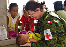 Lieutenant (Navy) Melanie Espina, doctor for the 1st Canadian Field Hospital, Petawawa, and member of the Canadian Armed Forces Disaster Assistance Response Team, examines a local baby during Operation RENAISSANCE, in Sara, Philippines on November 21, 2013. Photo: MCpl Marc-Andre Gaudreault, Canadian Forces Combat Camera IS2013-2006-058