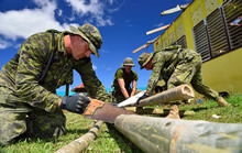 Gunner Shane Bristow (front) from 2 Royal Canadian Horse Artillery (2 RCHA), Petawawa, Corporal Joel Majaralie (middle) from 2 Combat Engineer Regiment, Petawawa and Gunner Nicholas Hearty from 2 RCHA, Petawawa cuts bamboo poles to build an evacuation shelter to let kids recover their classrooms that is currently used by typhoon Haiyan evacuees during Operation RENAISSANCE, in Pontevedra, Philippines on November 24, 2013. Photo: MCpl Marc-Andre Gaudreault, Canadian Forces Combat Camera IS2013-2006-091