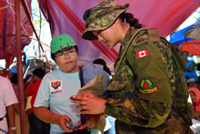 Lieutenant Sharon Ong, from 5e Régiment du génie de combat, Valcartier and Liaison Officer for the Disaster Assistance Response Team, exchanges information with a Municipal Social Welfare Department Office representative in order to assess the needs of the local population during Operation RENAISSANCE in Estancia, Philippines on November 25, 2013. Photo: MCpl Marc-Andre Gaudreault, Canadian Forces Combat Camera IS2013-2006-103