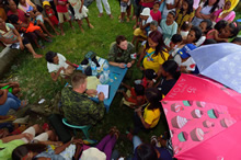 A medical group from the Canadian Armed Forces Disaster Assistance Response Team proceeds with patient triage during Operation RENAISSANCE, in Sara, Philippines on November 26, 2013. Photo: MCpl Marc-Andre Gaudreault, Canadian Forces Combat Camera IS2013-2006-106