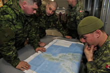 Private Sullivan, Master Corporal Beckwith, Corporal Brown and Corporal McGuire, members of the Disaster Assistance Response Team, study a map of the Philippine Islands that were ravaged by Typhoon Haiyan, at Canadian Armed Forces Base Trenton on November 13, 2013. Photo IS2013-3042-03: MCpl Patrick Blanchard, Canadian Forces Combat Camera