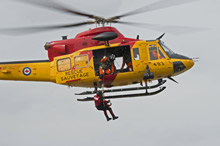 Lake Simcoe, Ontario. 5 May 2015 - A flight engineer lowers a Search and Rescue Technician from 424 (T&R) Squadron of 8 Wing Trenton to the ground from a Griffon helicopter during TIGER EX 2015 at the Lake Simcoe Airport. (Photo: Master Corporal Lori Geneau, 8 Wing Imaging)