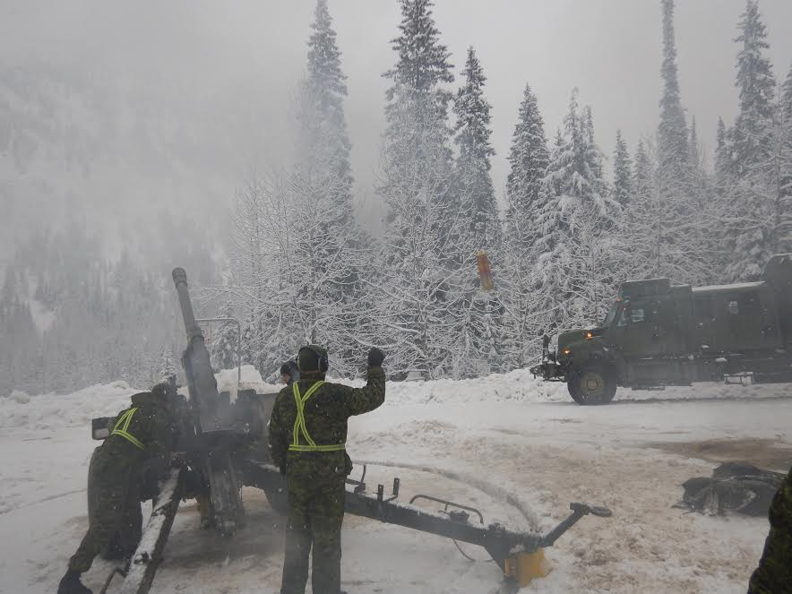 Shell casings fly as troops on Operation PALACI fire rounds to clear the avalanche pathways in Rogers Pass that transect the Trans-Canada Highway and CP Rail lines.