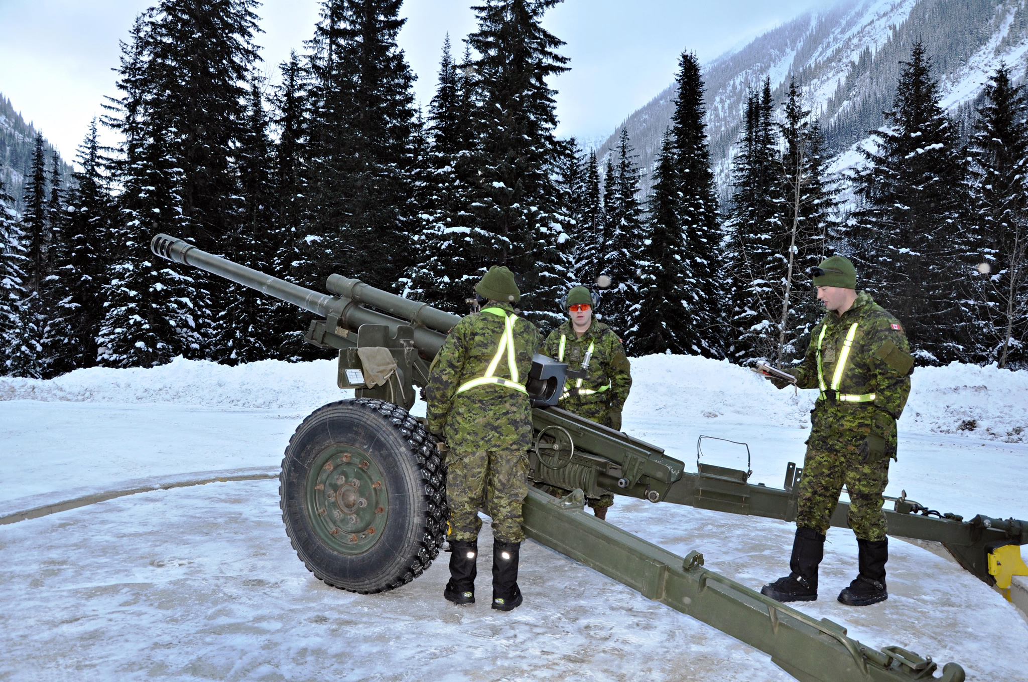Three soldiers load a large gun aimed at the mountains.