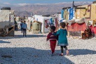 Two Syrian children walk through the Dalhamiye informal settlement for Syrian refugees in Lebanon on December 15, 2015