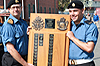 Reviewing Officer Capt(N) Timothy Gijzen presents the Commandant's Trophy to the RAVEN program's Top Student, Ordinary Seaman Perry Assu of Comox, B.C., during the program's graduation parade on August 21, 2014 at CFB Esquimalt.