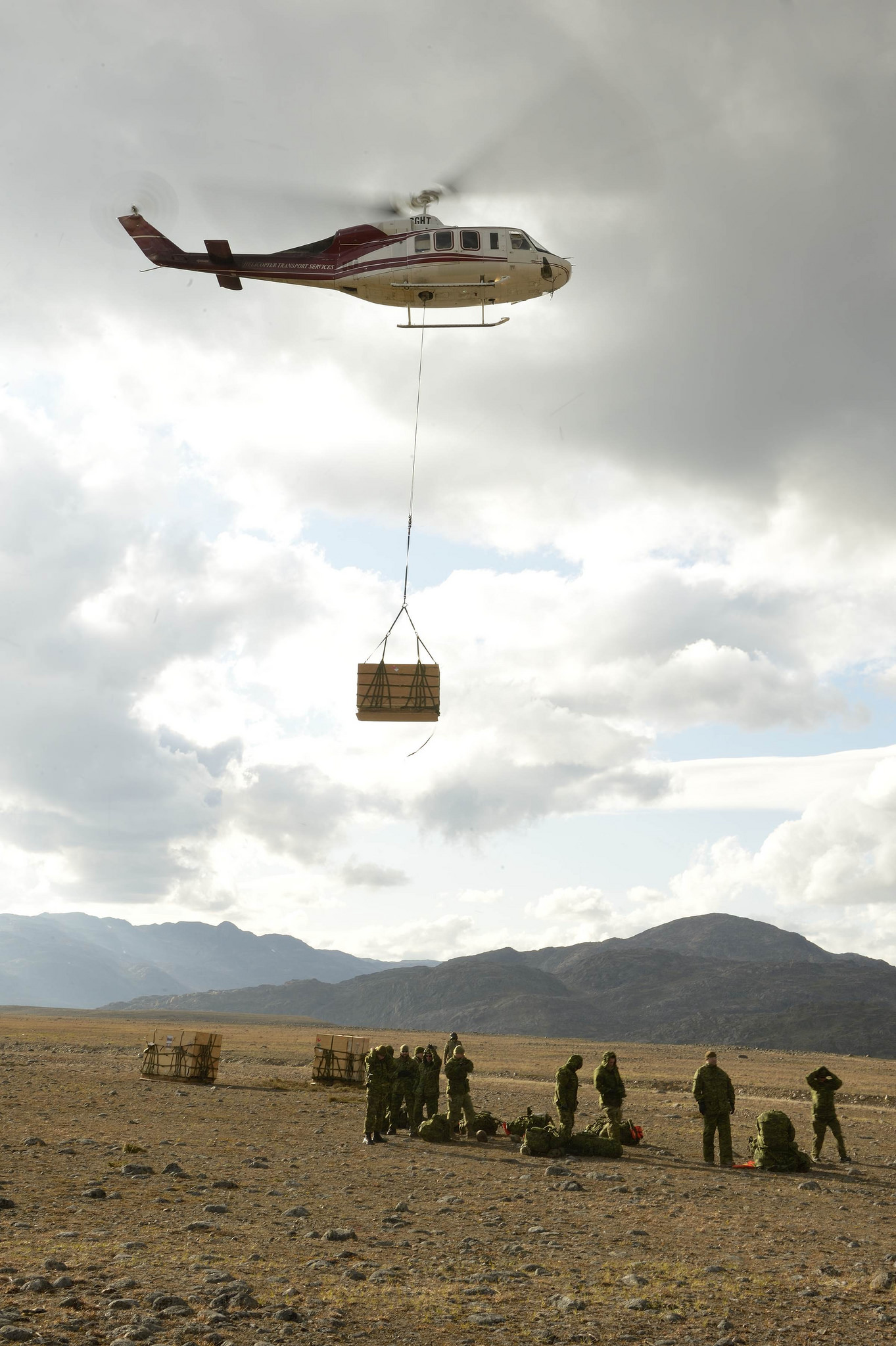 A crate attached to a helicopter