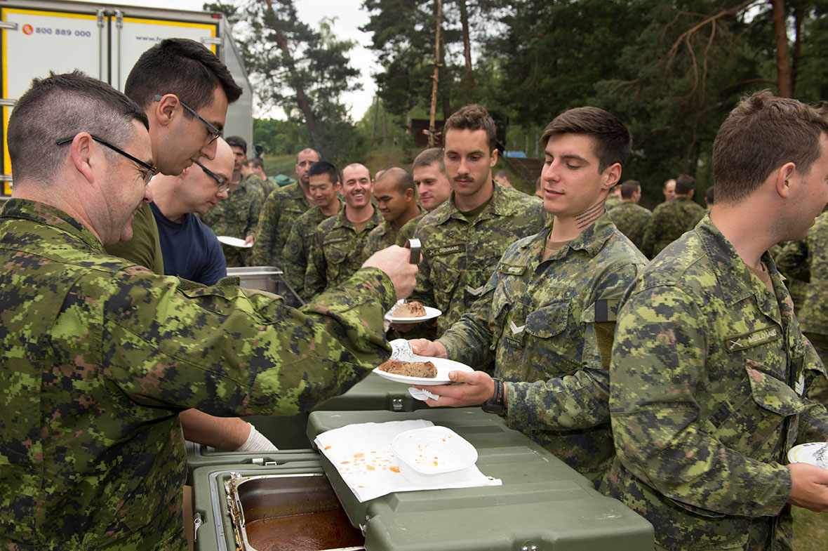 Warrant Officer Patrice Massé (left) serves dinner to the soldiers of the Operation REASSURANCE Land Task Force (LTF) during Exercise ANAKONDA, a multinational military exercise involving 23 nations, in Wȩdrzyn, Poland on June 12, 2016. The Canadian soldiers are deployed to Central and Eastern Europe as part of the LTF to support regional NATO assurance measures and enhance interoperability with NATO allies. (Photo: Master Corporal Andrew Davis, Operation REASSURANCE Land Task Force Imagery Technician)