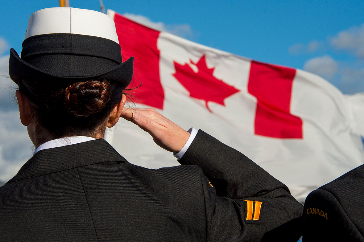 A female sailor is seen from behind while she salutes a Canadian flag