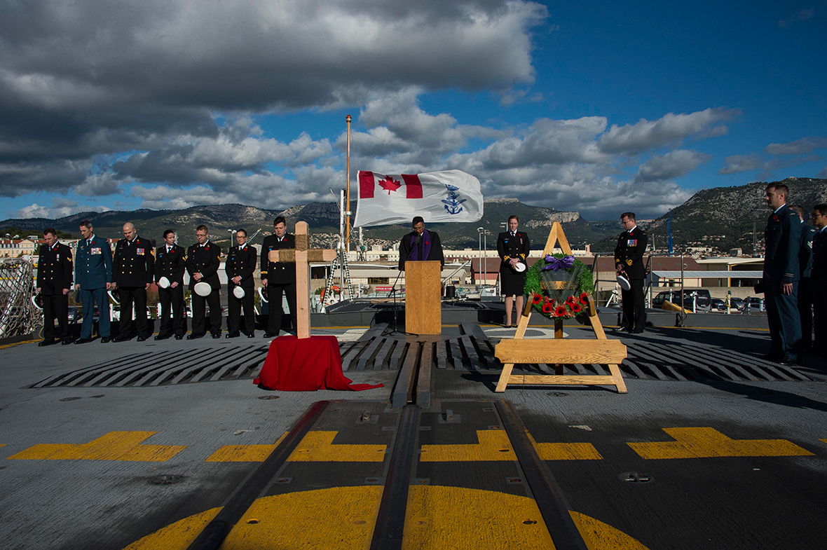Toulon, France. November 11, 2016 – Padre Lieutenant (Navy) Haupi Tombing (center) gives prayers onboard Her Majesty's Canadian Ship (HMCS) CHARLOTTETOWN as the ship commemorates Remembrance Day while alongside in Toulon, France during OP REASSURANCE. (Photo: Cpl Blaine Sewell, Formation Imagery Services)