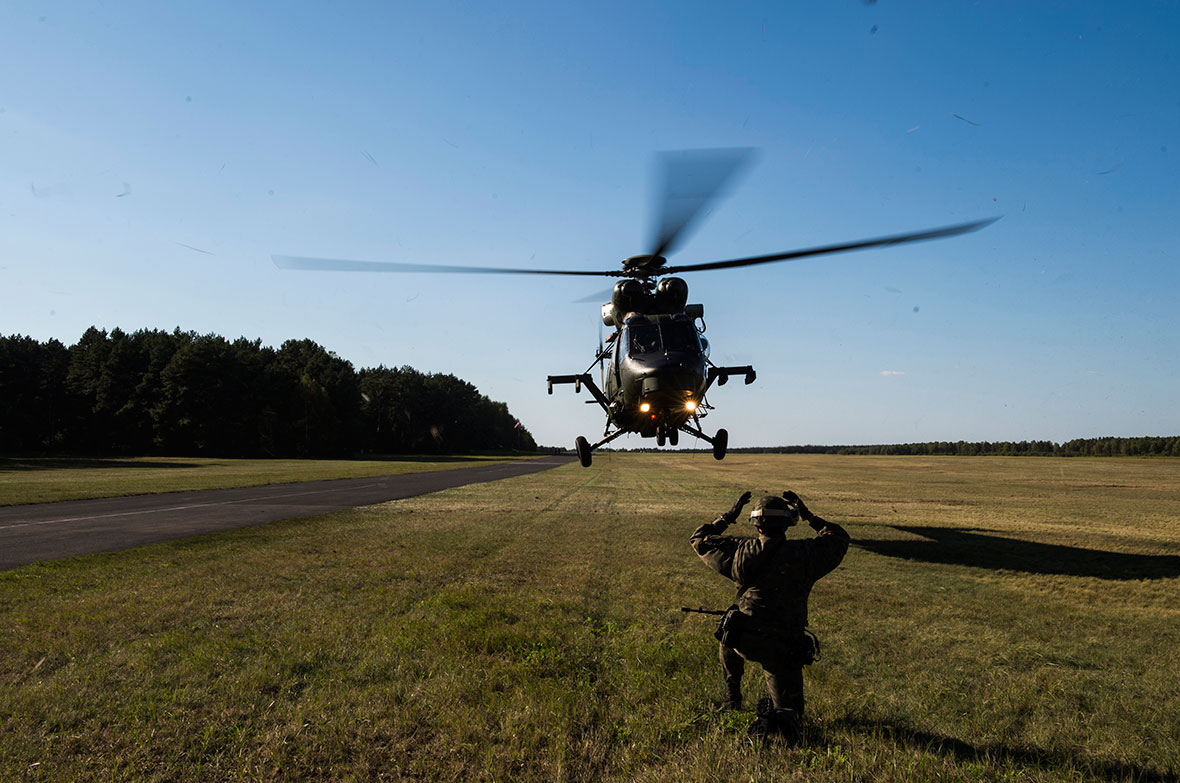 A Polish soldier guides in a W3W Falcon helicopter for a landing in Drawsko Pomorskie Training Area, during Operation REASSURANCE on September 14, 2016. (Photo: Cpl Jay Ekin, Operation REASSURANCE Land Task Force Imagery Technician)