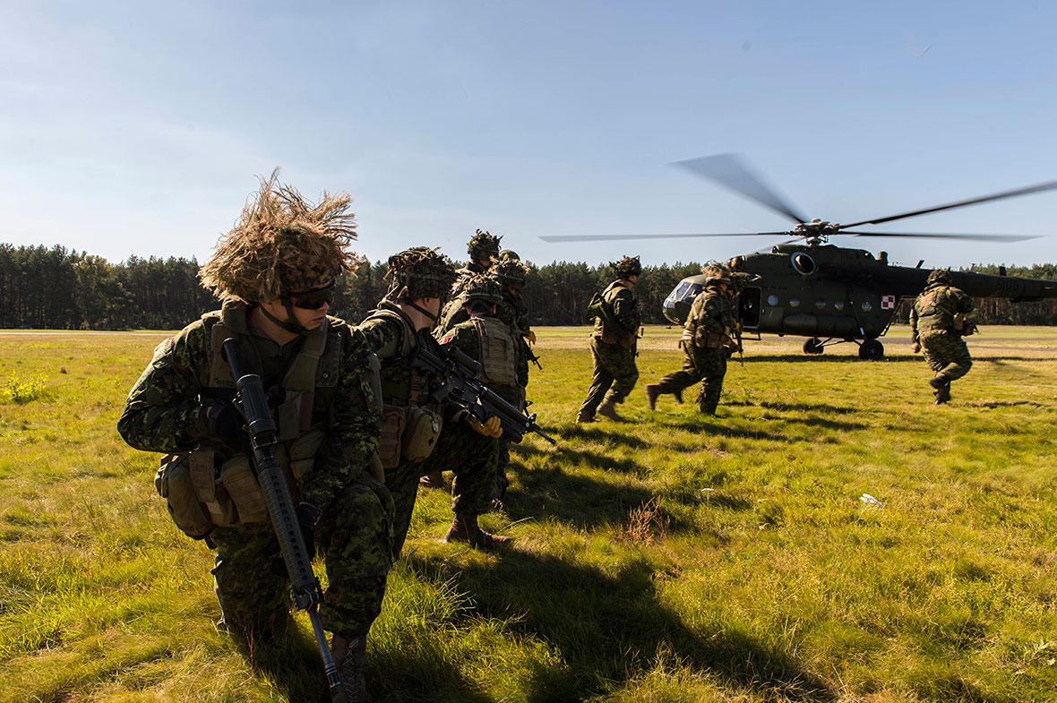 Soldiers run in a field to board a helicopter.
