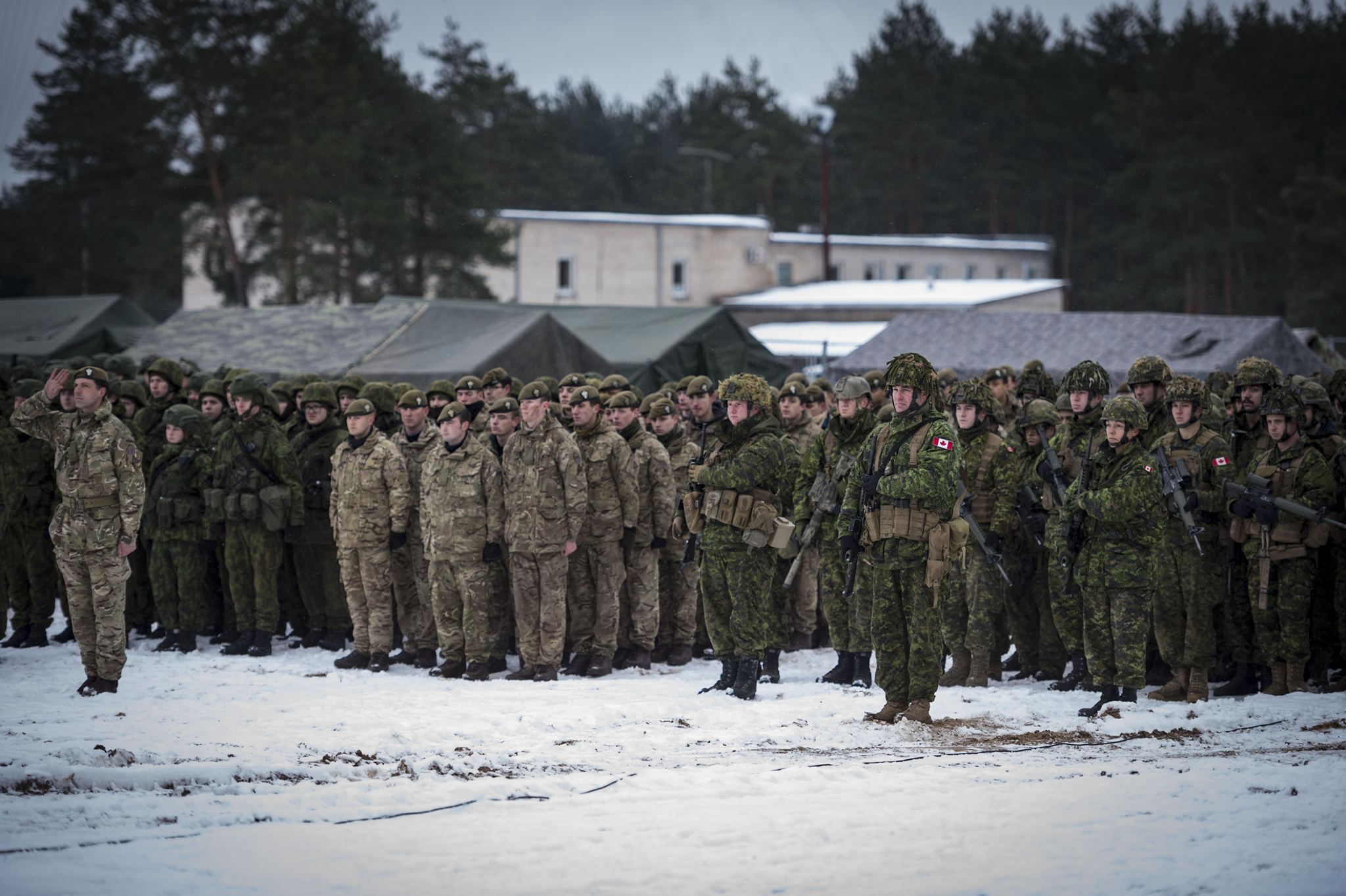 Members of the Land Task Force Rotation 6 stand on parade for the closing ceremony of Exercise IRON SWORD in Silvestras Zukauskas Pabrade training area, Lithuania, during Operation REASSURANCE on December 2, 2016. (Photo: Corporal Jay Ekin, Operation REASSURANCE Land Task Force Imagery Technician)
