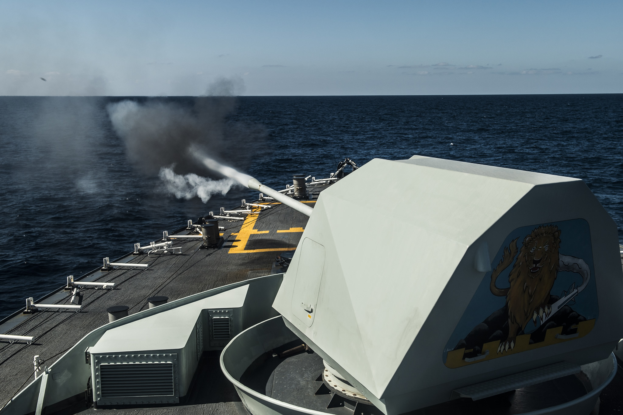 A large gun fires at a target from a ship
