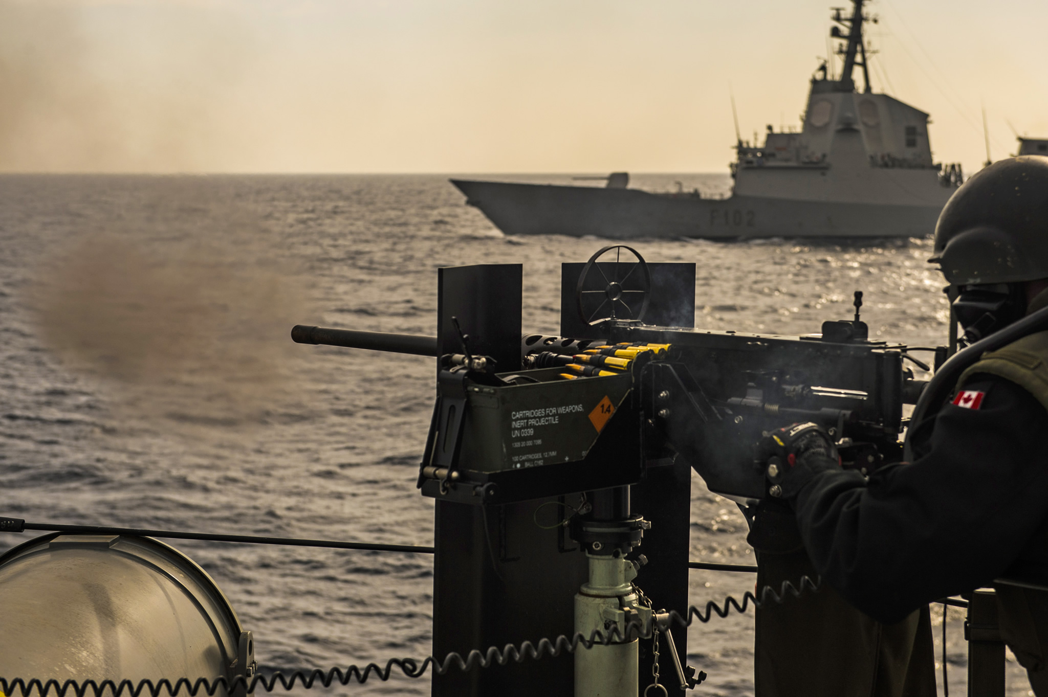 Mediterranean Sea. March 1, 2017 – A .50 Calibre Heavy Machine Gun operator onboard Her Majesty's Canadian Ship St. John's fires warning shots ahead of the Spanish Frigate JUAN DE BORBON during an exercise as they transit the Mediterranean Sea, during Operation REASSURANCE. (Photo: Leading Seaman Ogle Henry, Formation Imaging Services)