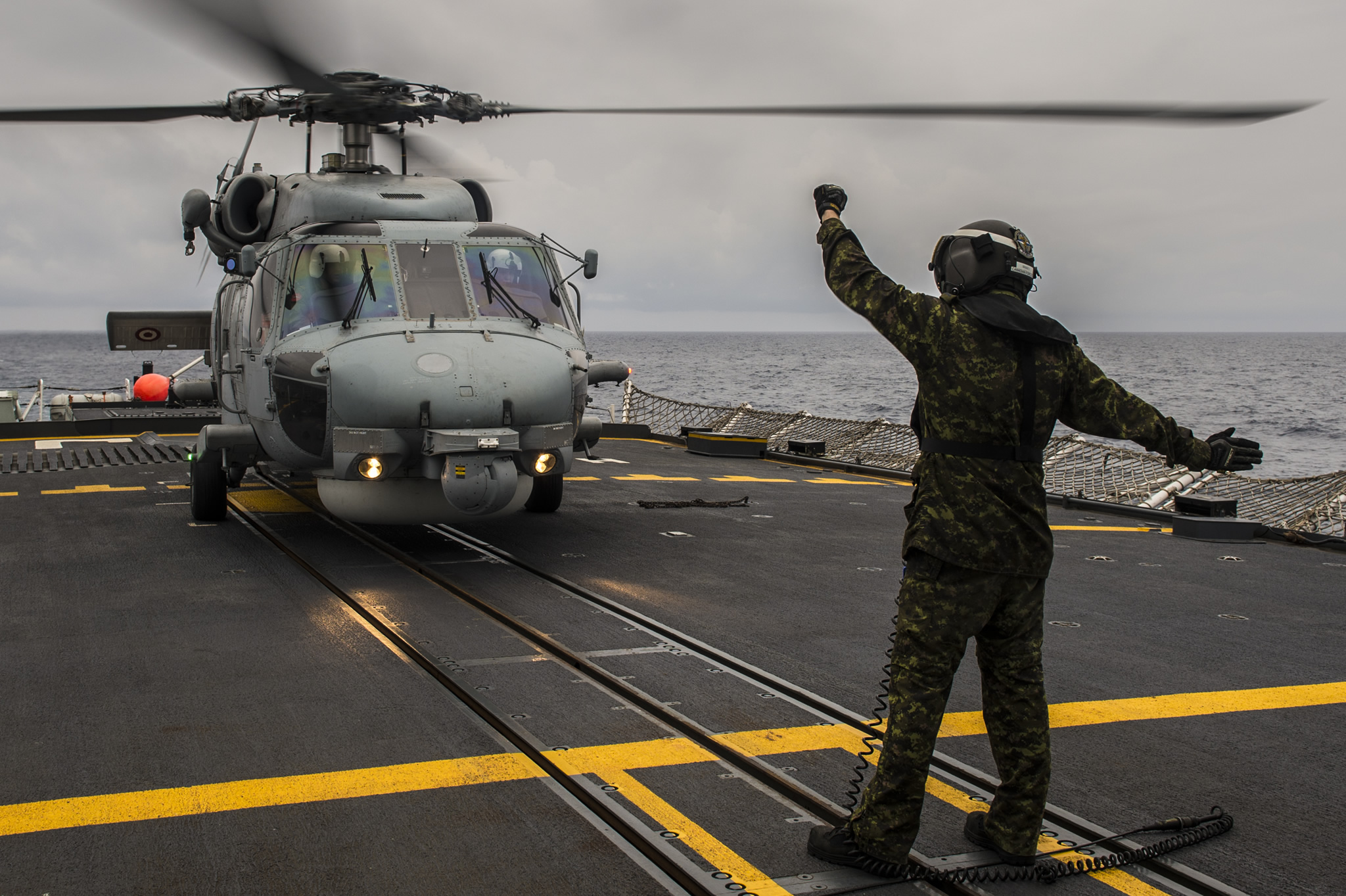 A person holds their arms in the air in front of a helicopter on a ship
