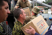 Military members move supplies onto a ship during Operation RENDER SAFE in September 2016. (Photo: Australian Army)