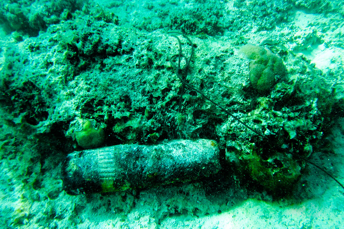Solomon Islands. September 24, 2016 – A team of Royal New Zealand Navy and Royal Canadian Navy divers use a 75mm unexploded projectile to mark the location of a 100lb unexploded air-dropped bomb near Aeaun Island in the Solomon Islands on 24 September, 2016, during Operation RENDER SAFE. (Photo by Australian Defence Forces)