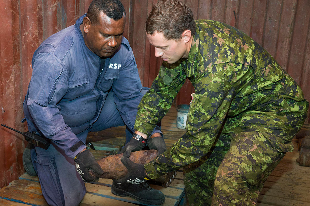 Royal Solomon Islands Police Force Sergeant Morris Ale (left) and Canadian Army soldier Sergeant Steven Krose lift unexploded munitions to be X-rayed during Operation RENDER SAFE 2016 in the Solomon Islands, September 2016. (Photo: Australian Defence Force).