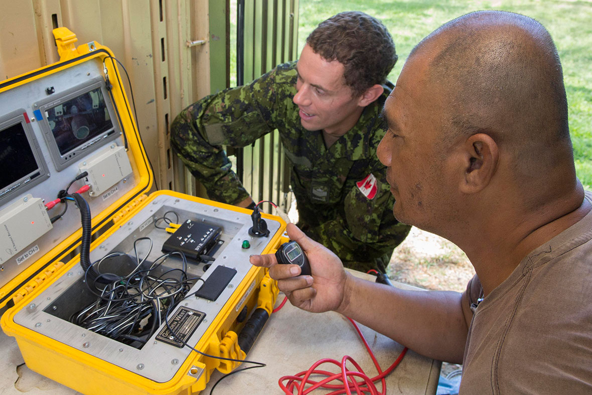 Royal Solomon Islands Police Force (RSIPF) Sergeant Hedley Manamua (right) shows Canadian Army soldier Sergeant Steven Krose how the Royal Solomon Islands Police Force disposes of unexploded remnants of war during Operation RENDER SAFE 2016 in the Solomon Islands, September 2016. (Photo: Australian Defence Force).