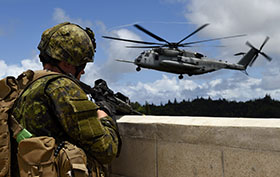 Kahaku Training Area Hawaii, U.S.A. 26 July 2014 - Corporal Alex Stickland from 3rd Battalion, Princess Patricia's Canadian Light Infantry, provides perimeter security as a U.S. Marines CH-53 Super Stallion helicopter lands at Kahuku Training Area Hawaii for non-combatant evacuation operation training during Exercise Rim of the Pacific (RIMPAC). (Photo: Sgt Matthew McGregor, Canadian Forces Combat Camera)