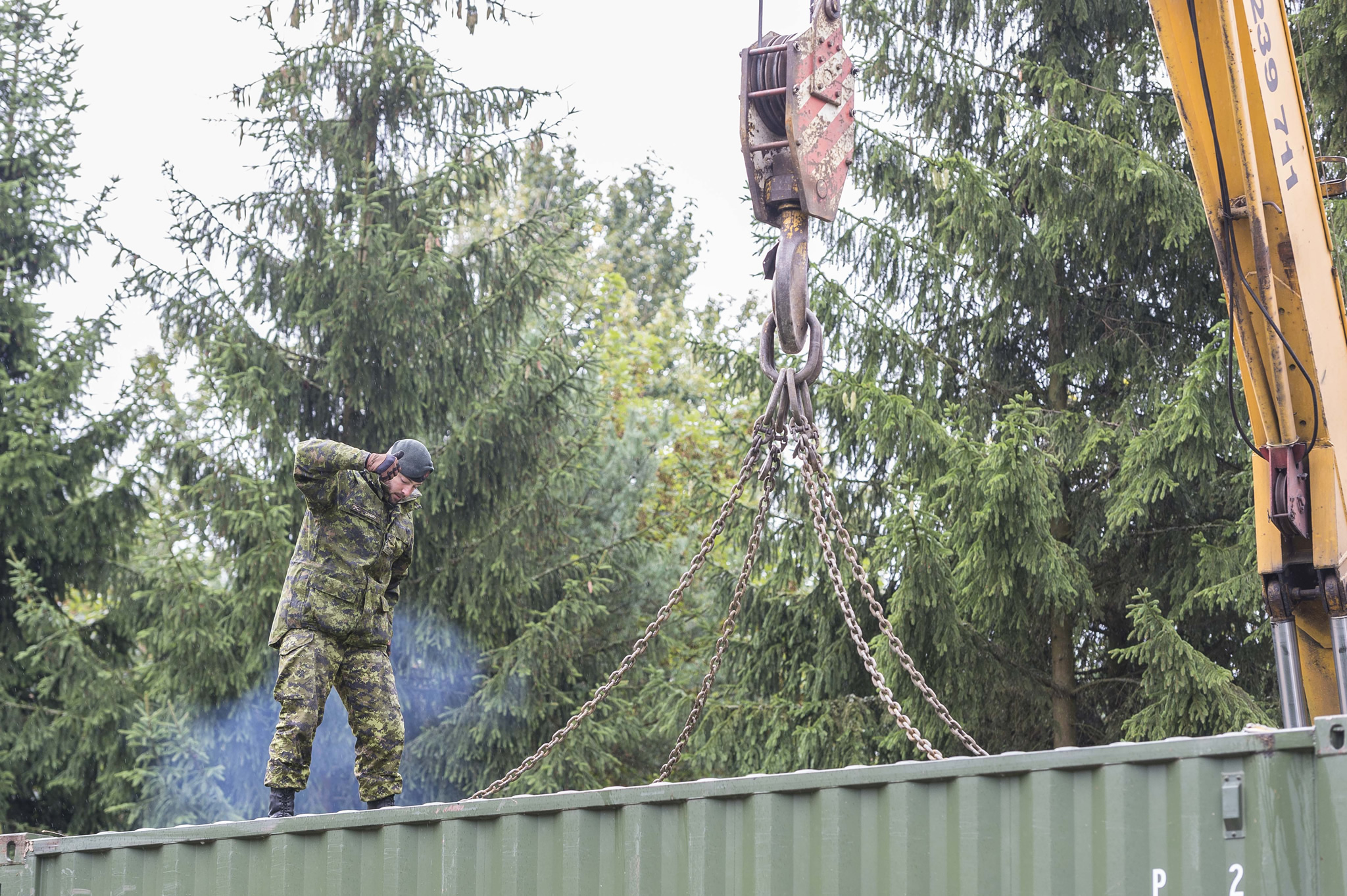 Glebokie, Poland. 11 September 2015 - Corporal Pierre-Michel Landry signals the crane operator after loading a sea container on a flatbed for transportation to EX SILVER ARROW during Operation REASSURANCE. (Photo: Corporal Nathan Moulton, Land Task Force Imagery, OP REASSURANCE)